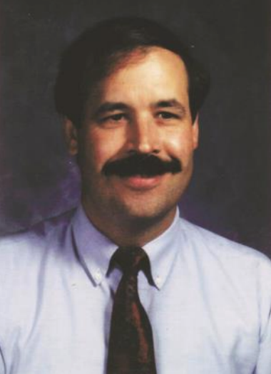 Joseph E. Zins - A light-skinned, male-presenting person with a mustache wearing a tie